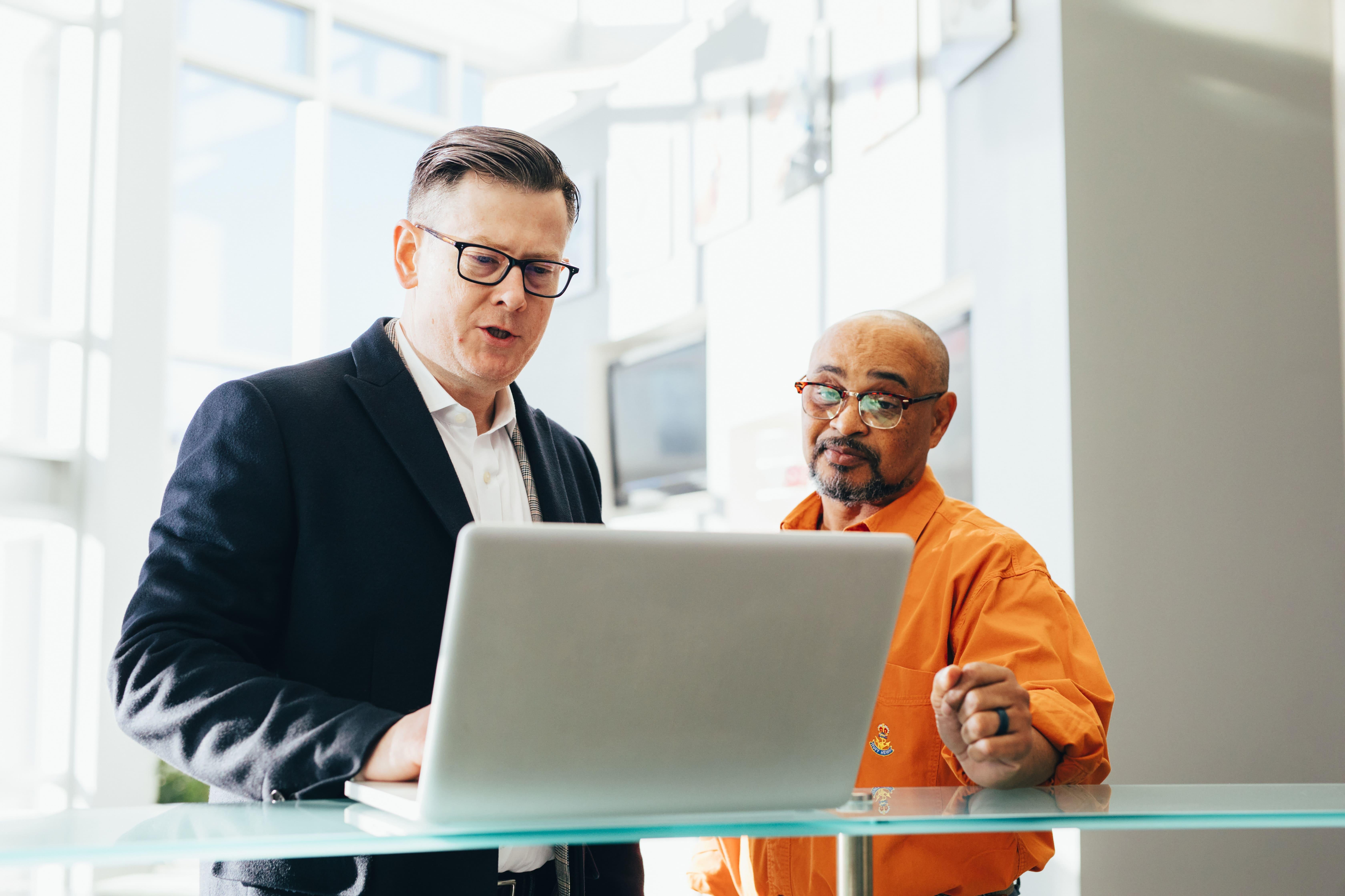 white-man-suit-black-man-computer-desk-trading-robo-advisor-roboadviser-finance