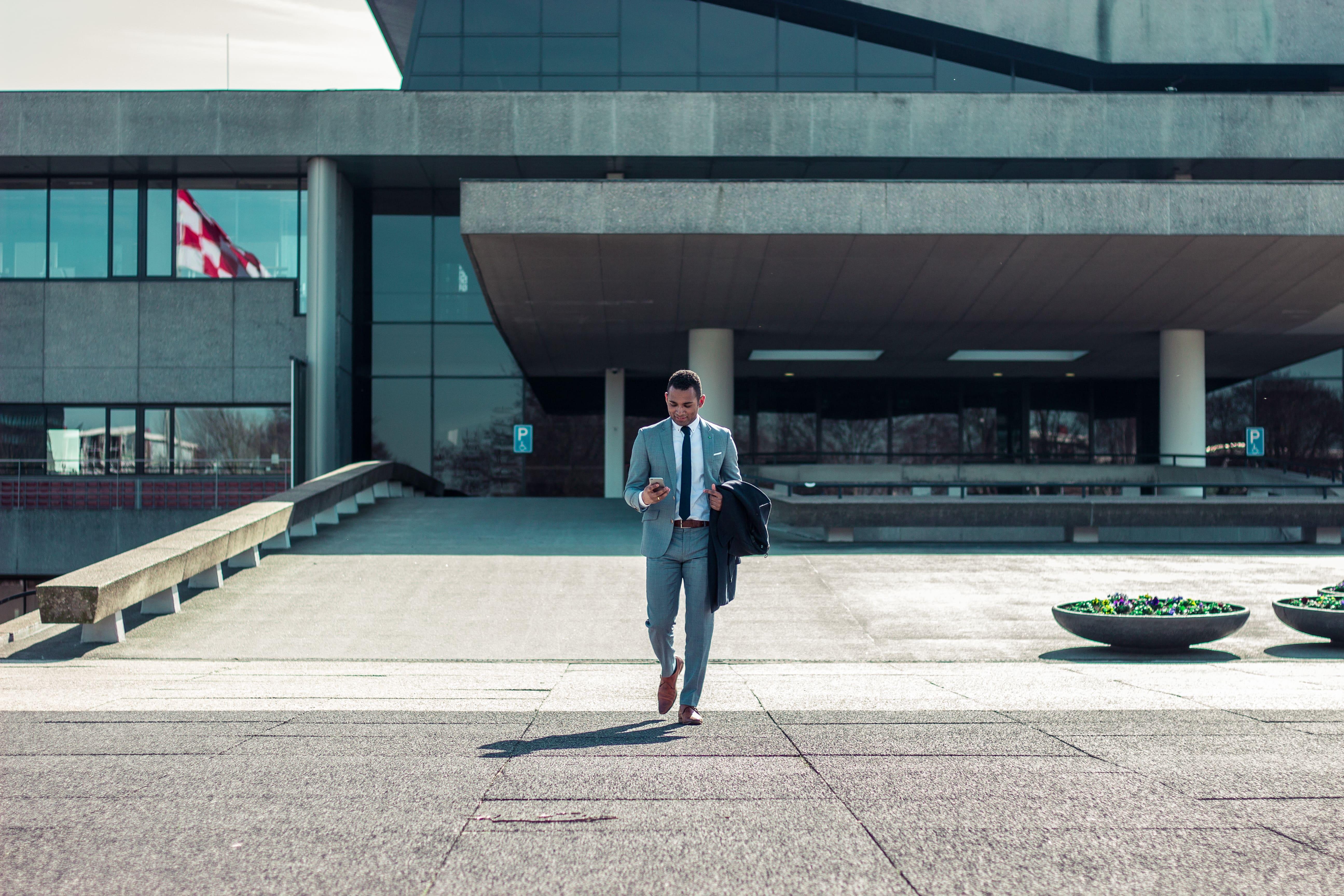 man-walking-business-suit-phone-impact-of-covid-on-broker-dealers